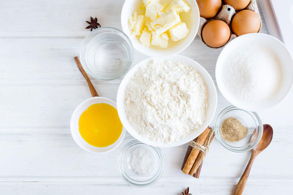 flour, sugar, eggs and butter on table